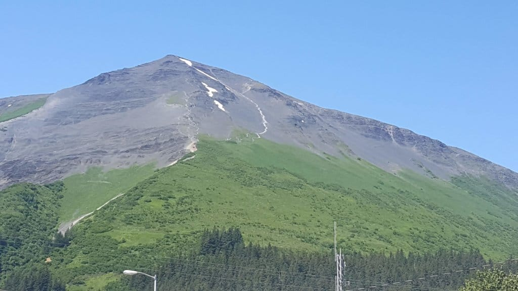 Big mountain with greenery at the bottom and rock at the top