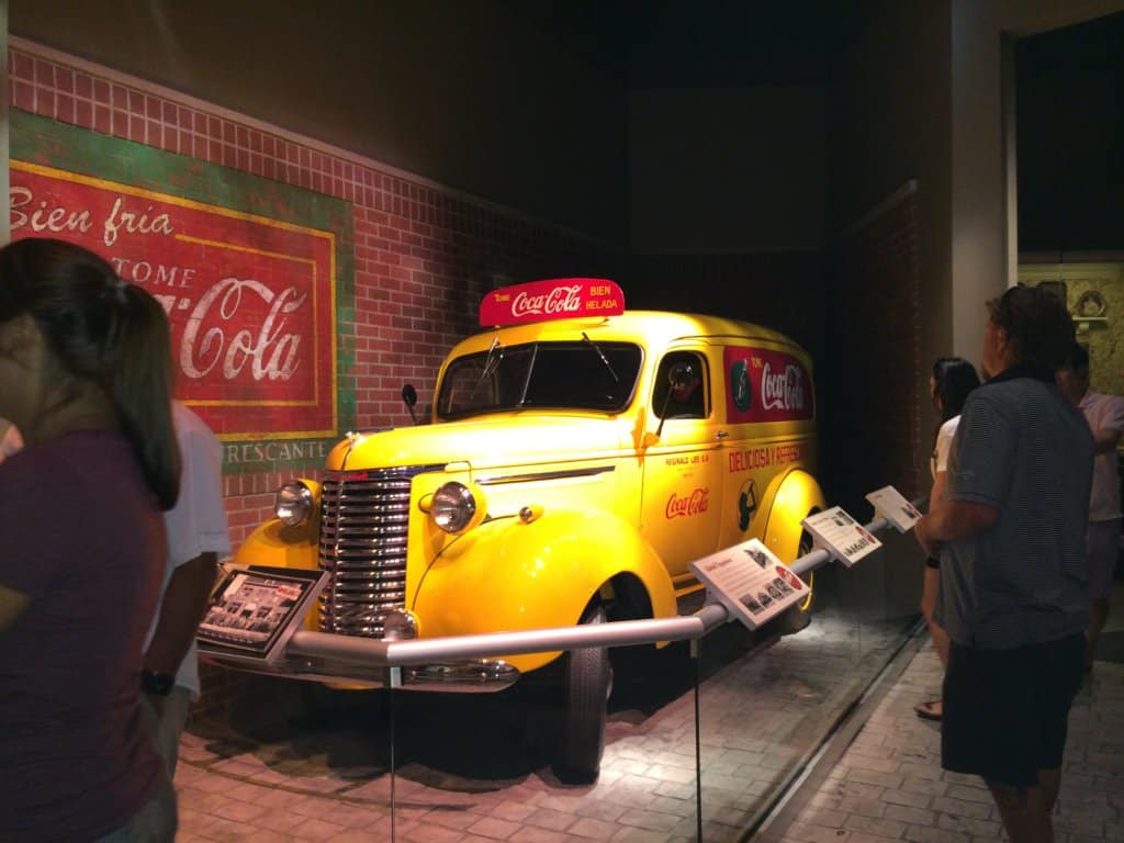 a very old yellow delivery truck with the words Coca-Cola