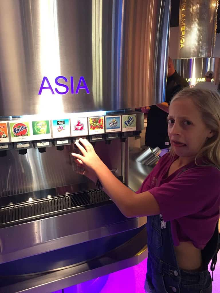 a young girl standing beside a soda fountain with a sour face