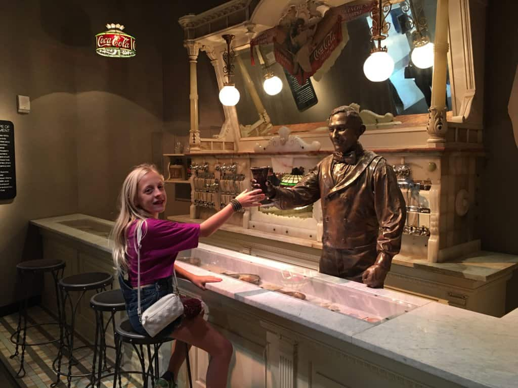 a young girl giving cheers to a statue behind a bar