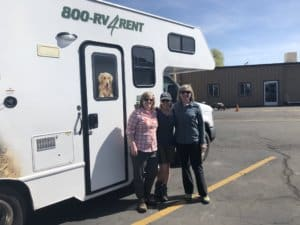 3 women standing in front of a RV